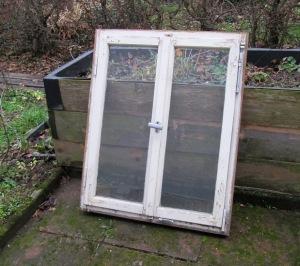 Altes Fenster lehnt im Garten an ein Hochbeet