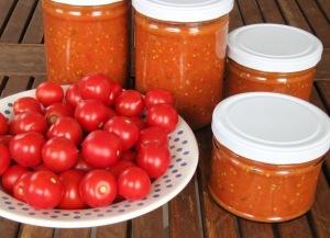 Frische Tomaten auf einem Teller. Daneben Schraubdeckelgläser mit Tomatensoße.