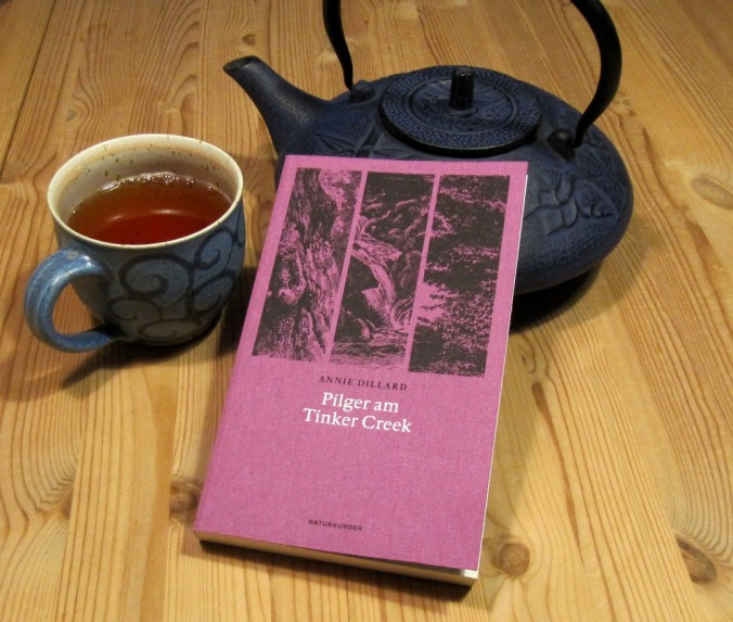 Ein Buch lehnt an eine gusseiserne Teekanne. Daneben eine halbvolle Teetasse.